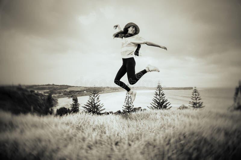 La mujer que salta delante de una playa hermosa en Australia imágenes de archivo libres de regalías
