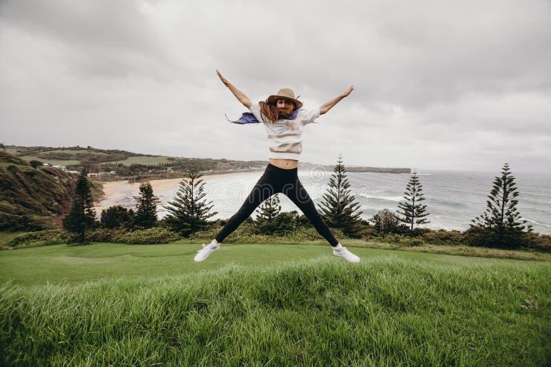 La mujer que salta delante de una playa hermosa en Australia imagenes de archivo