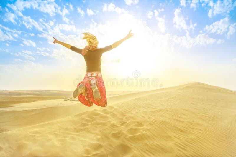 La mujer que salta en el desierto de Qatar foto de archivo