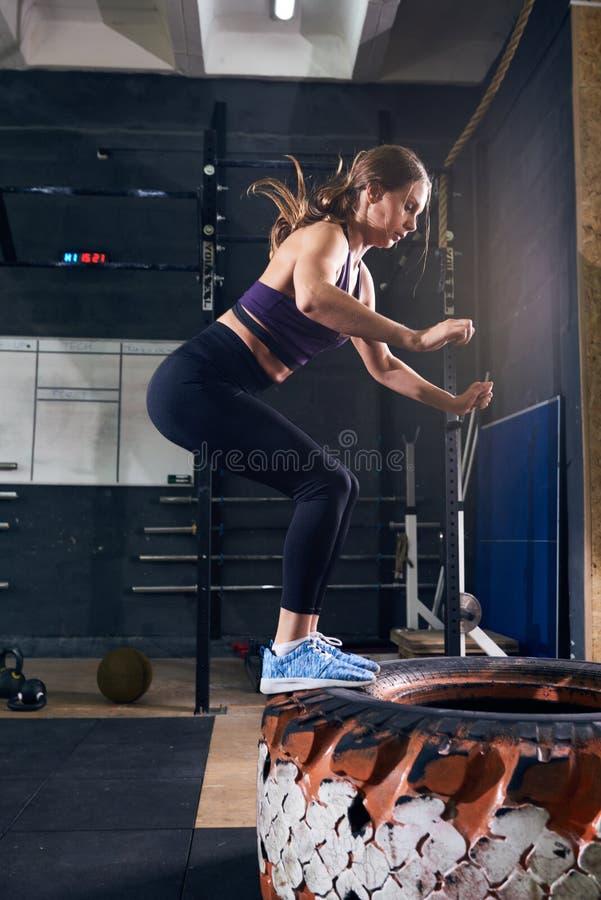 La mujer que salta en el neumático en el gimnasio de CrossFit foto de archivo