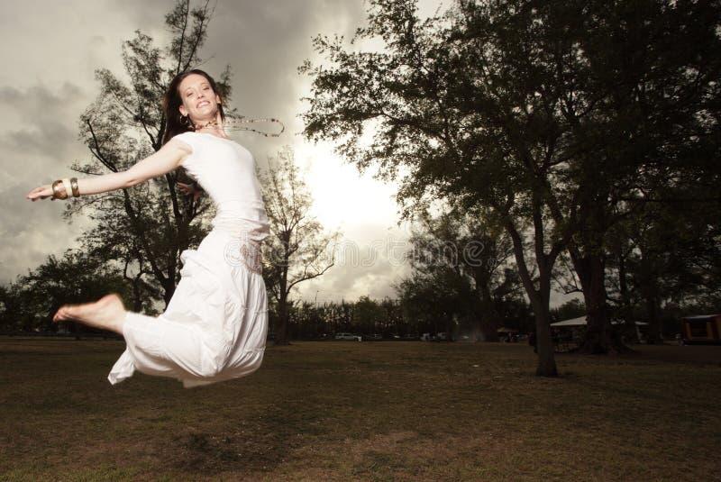 La mujer que salta en el parque imagen de archivo