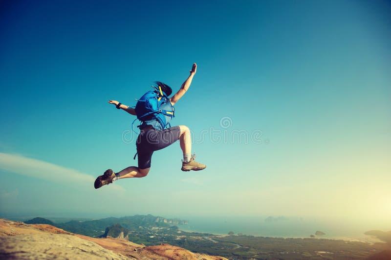 la mujer que salta en el top de la montaña rocosa fotografía de archivo libre de regalías