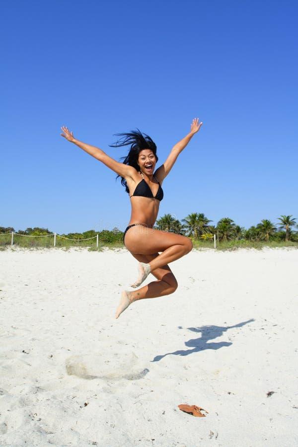 La mujer que salta en la arena imagen de archivo libre de regalías