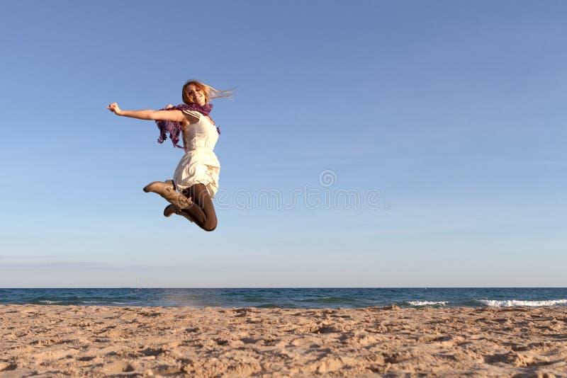 La mujer que salta en la playa imagenes de archivo
