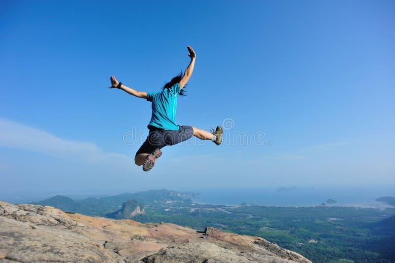 La mujer que salta en pico de montaña rocosa fotos de archivo libres de regalías