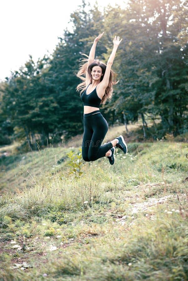 La mujer que salta en prado imagen de archivo libre de regalías