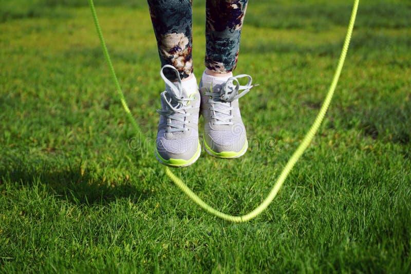 la mujer que salta en una cuerda que salta en parque foto de archivo