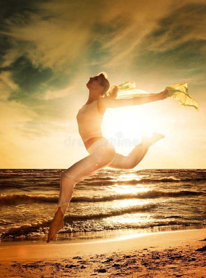 La mujer que salta en una playa fotos de archivo