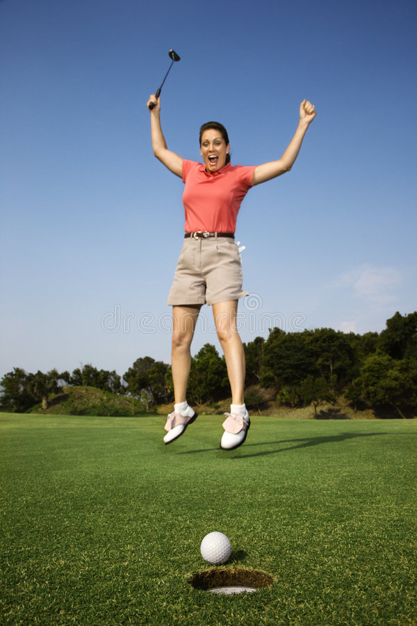 La mujer que salta sobre buen tiro de golf. fotografía de archivo