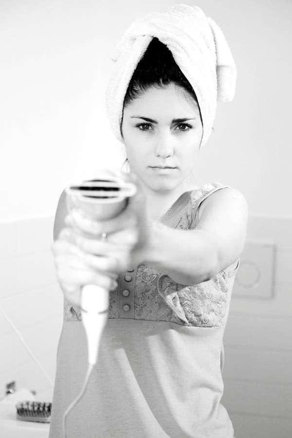 La mujer que señala el secador del soplo le gusta blanco y negro serio del arma fotografía de archivo
