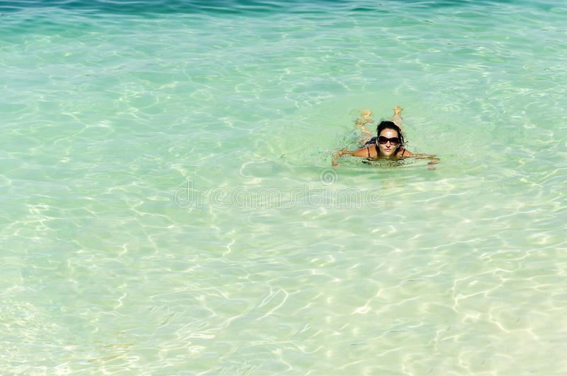 La mujer que se relaja en turquesa riega en la playa tropical imagenes de archivo