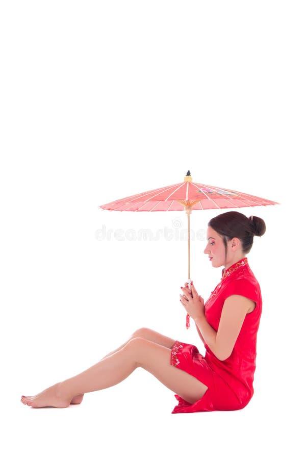 La mujer que se sienta atractiva joven en japonés rojo se viste con el umbrel