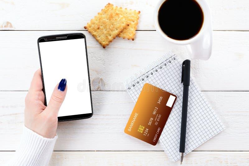 La mujer que se sienta en la tabla y paga la compra con smartphone imágenes de archivo libres de regalías