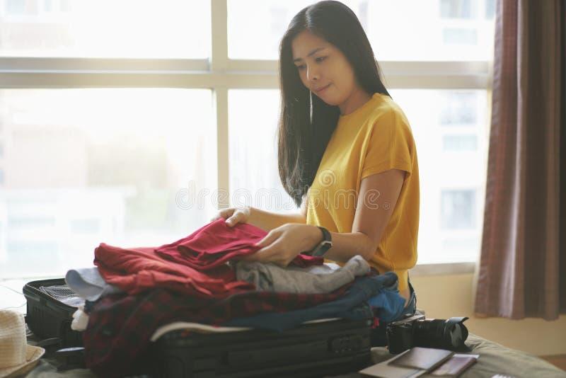 La mujer que se sienta en la ropa de la cama y del paquete en bolso de la maleta en dormitorio, se prepara para el nuevos viaje y fotografía de archivo