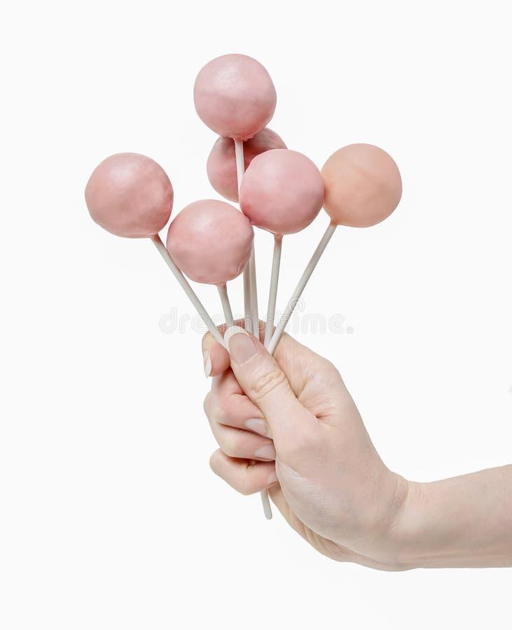 La mujer que se sostiene alguna torta rosada hace estallar a disposición foto de archivo