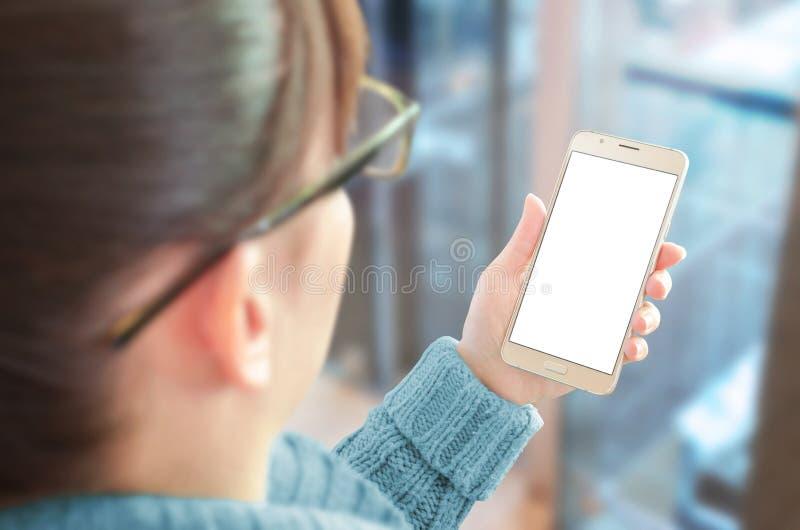 La mujer que sostenía el teléfono elegante con el espacio en blanco, blanco aisló la pantalla para la maqueta imagen de archivo libre de regalías