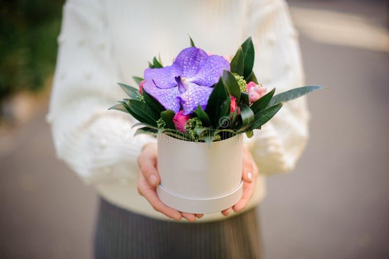 La mujer que sostenía una caja blanca de orquídea violeta con poco rosado subió foto de archivo libre de regalías