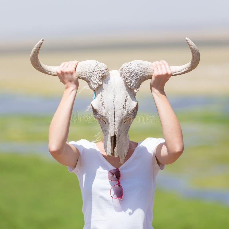 La mujer que sostiene un cráneo blanco del ñu que lo lleva le gusta una máscara en naturaleza en safari africano de la fauna foto de archivo libre de regalías