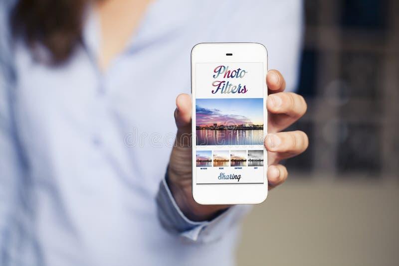 La mujer que sostiene un teléfono móvil con la foto filtra el app en el pedregal fotografía de archivo libre de regalías