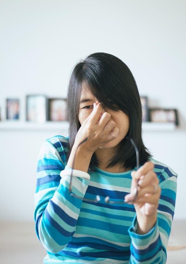 La mujer que sufre de la mano del dolor de ojo que sostiene las lentes y frota sus ojos de la nariz fuera de cansancio foto de archivo