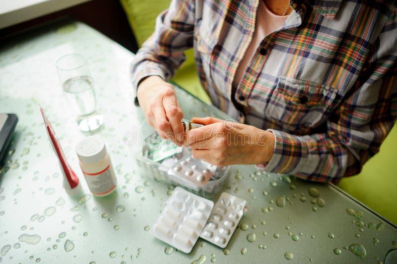 La mujer que tiene artritis reumatoide toma la medicina foto de archivo