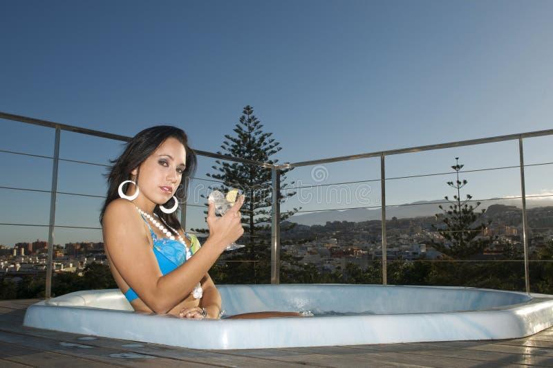 La mujer que tiene se relaja en Jacuzzi bajo el cielo azul imagen de archivo libre de regalías