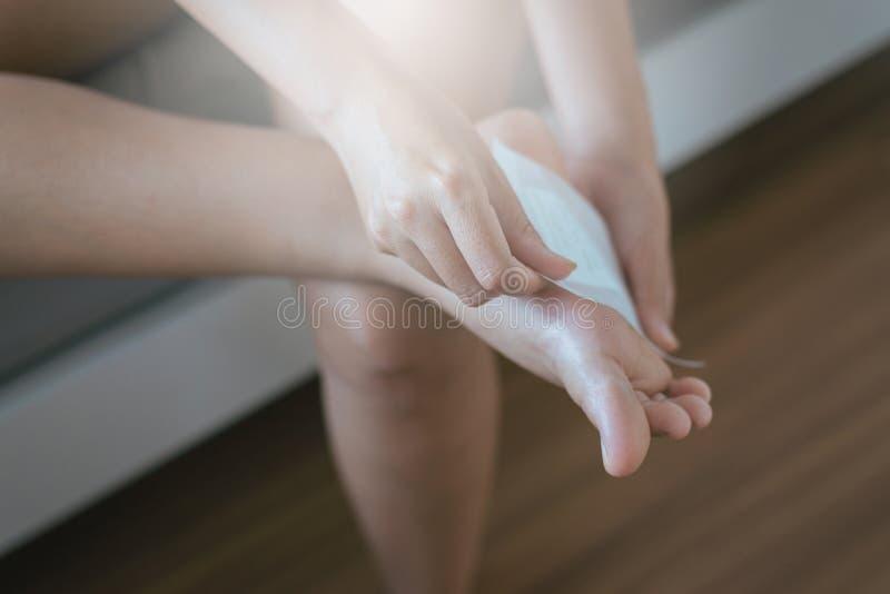 La mujer que usa el remiendo blanco para alivia dolor y relaja a pie el lenguado, pies de lesión imagen de archivo libre de regalías