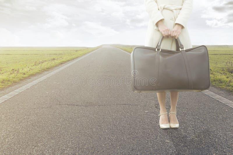 La mujer que viaja espera con su maleta en el borde de la carretera imagenes de archivo