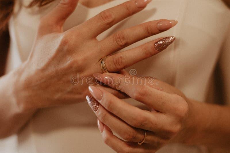 La mujer quita el anillo de oro de la mano imagenes de archivo