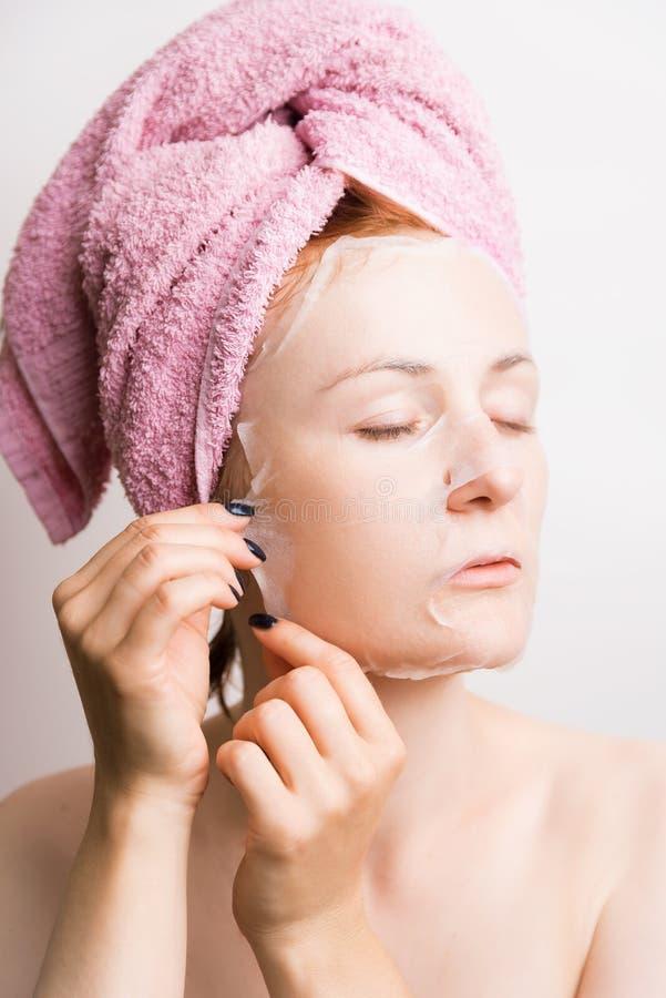 La mujer quita la máscara cosmética en cara en fondo ligero foto de archivo libre de regalías