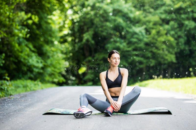 La mujer realiza estirar antes de deporte en parque al aire libre imágenes de archivo libres de regalías