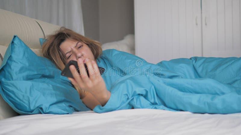 La mujer realmente durmiente despierta y mira el teléfono lo lanza y se cae dormido fotos de archivo libres de regalías