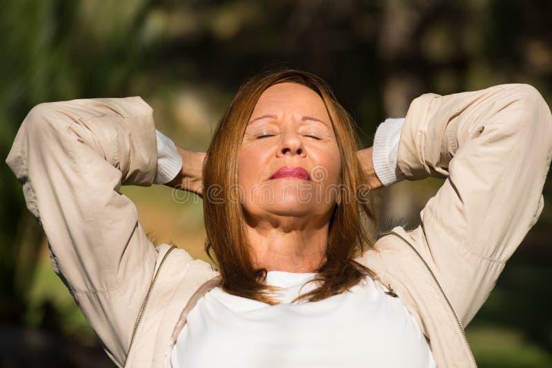 La mujer relajada feliz cerrada observa al aire libre foto de archivo libre de regalías
