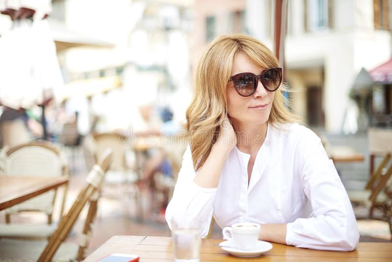 La mujer relajada goza de su café foto de archivo