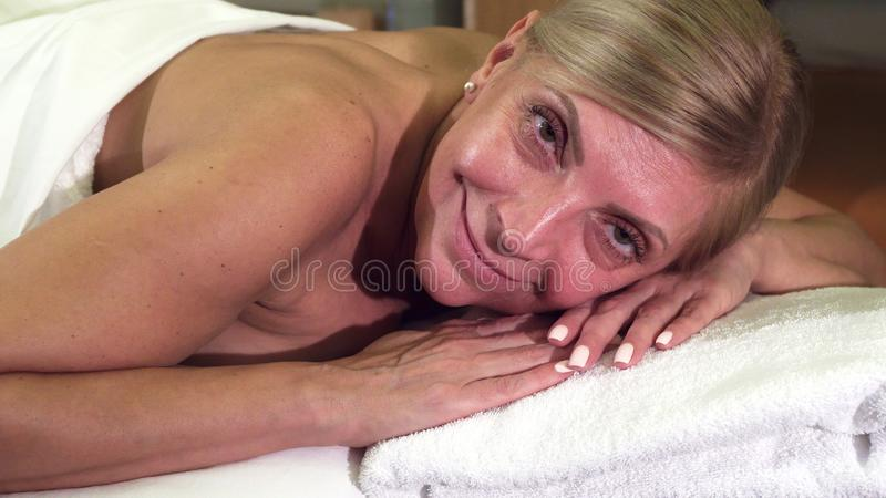 La mujer relajada miente en una tabla del masaje fotos de archivo