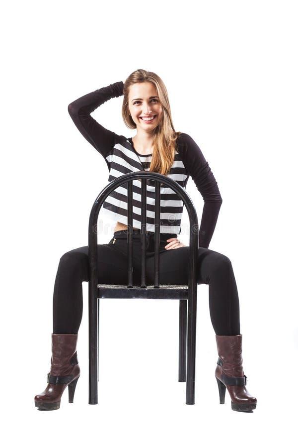 La mujer relajada que se sienta en una silla está sonriendo imagen de archivo