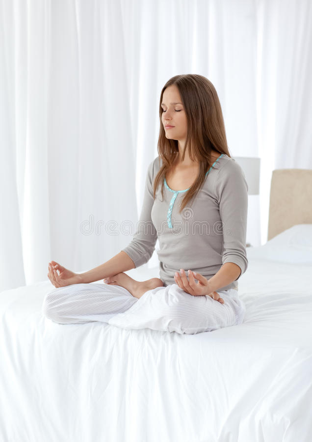 La mujer reservada que hace yoga ejercita en la cama fotos de archivo