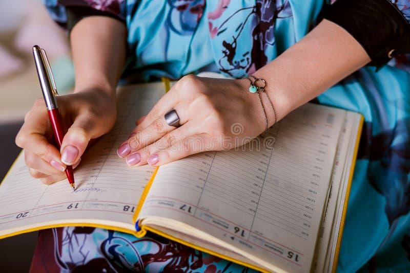 La mujer respetable está escribiendo notas y horario de planificación imagen de archivo libre de regalías