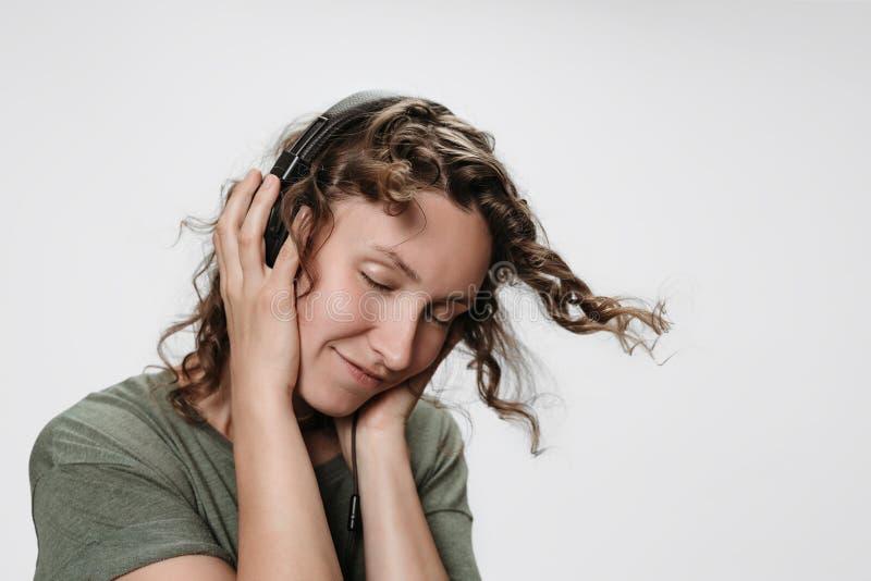La mujer rizada joven alegre despreocupada escucha m?sica preferida con la mano en sus auriculares imagen de archivo