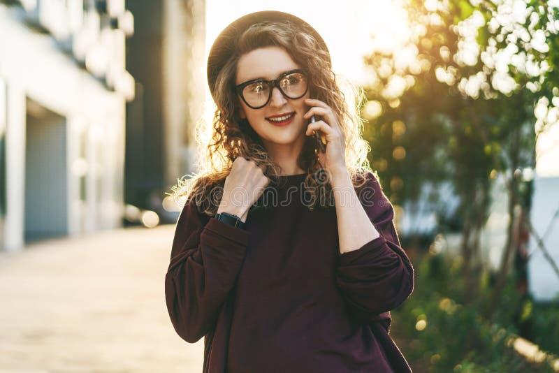 La mujer rizada joven en sombrero y vidrios de moda se está colocando en la calle de la ciudad y está hablando en el teléfono cel imágenes de archivo libres de regalías