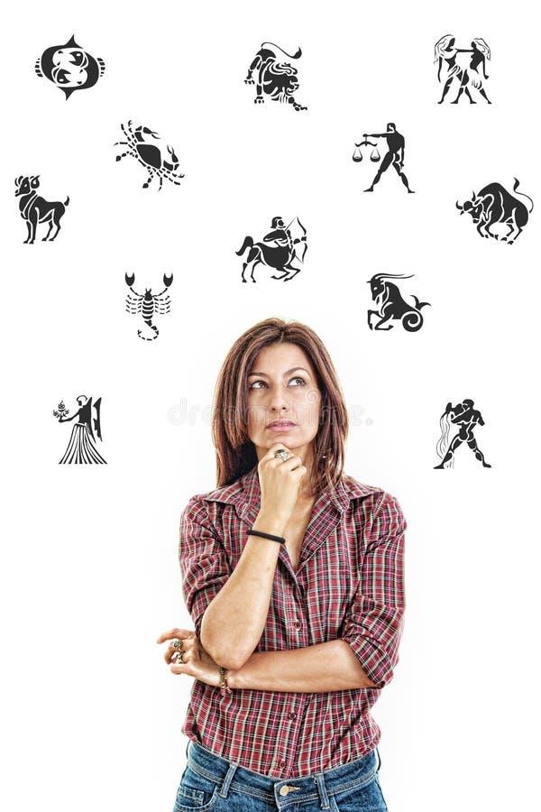 La mujer rodeada con el zodiaco firma cuidadosamente la mirada para arriba con fotos de archivo libres de regalías