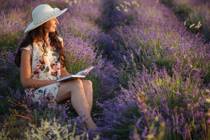 La mujer romántica se sienta con el libro en campo de la lavanda foto de archivo
