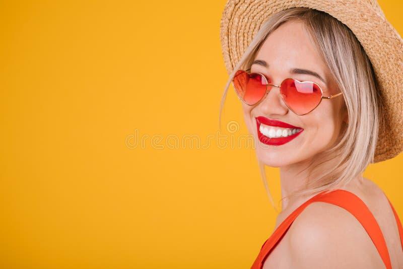 La mujer rubia adorable con los dientes grandes sonríe en sombrero de paja en fondo amarillo brillante Gafas de sol rosadas en fo imagen de archivo libre de regalías