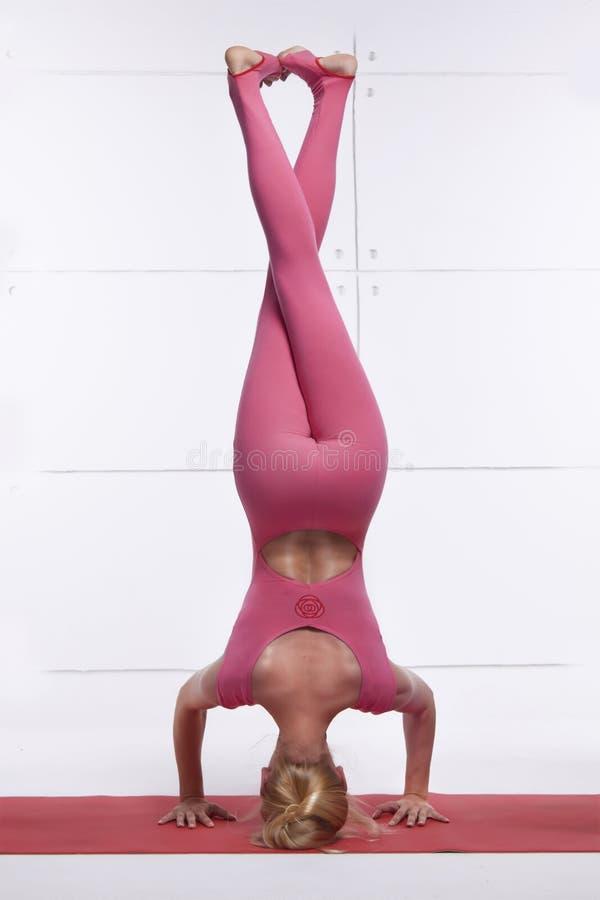 La mujer rubia atractiva atractiva hermosa que hace la yoga que se coloca en su cabeza con las piernas cruzadas relaja y abre el  fotos de archivo