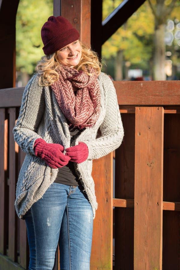 La mujer rubia atractiva en el parque está alegre sobre el otoño incluso imagen de archivo libre de regalías