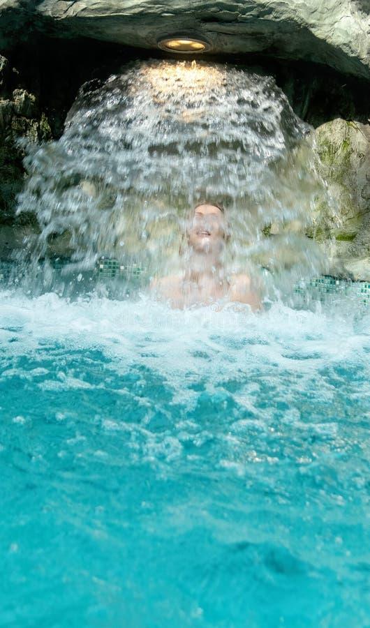 La mujer rubia atractiva joven en bikini rosado goza del agua que cae detrás de la cascada en el balneario imagen de archivo libre de regalías
