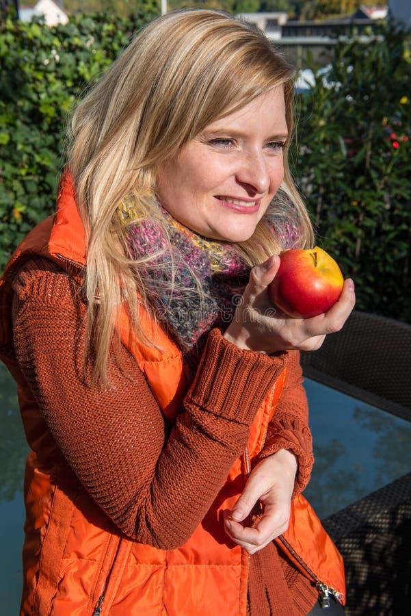 La mujer rubia atractiva tiene una manzana en su mano imagen de archivo libre de regalías