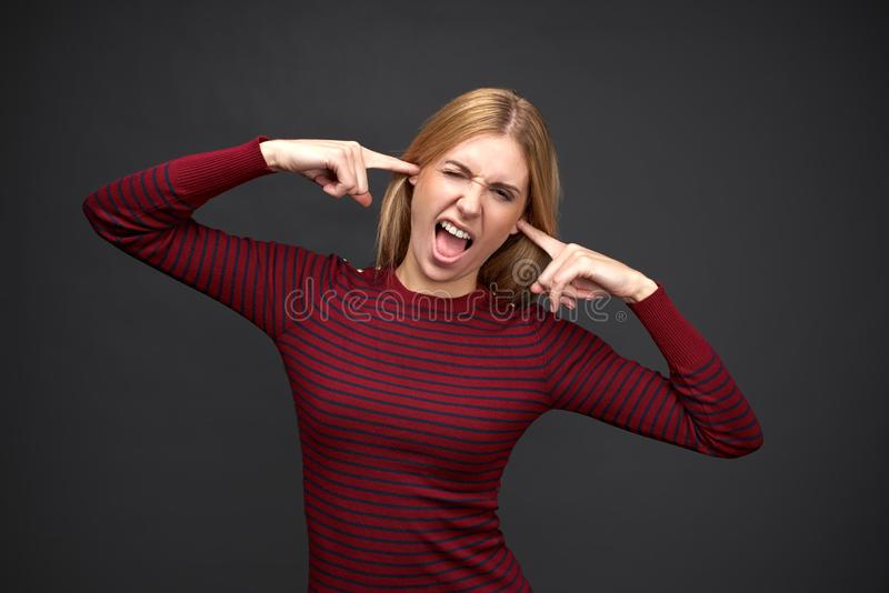 La mujer rubia atrevida joven en suéter rojo tapa sus oídos con los fingeres y abre su boca de par en par foto de archivo libre de regalías