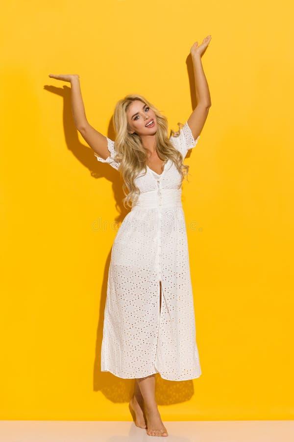 La mujer rubia bonita en el vestido blanco del verano se está colocando con los brazos aumentados y hablar imagen de archivo libre de regalías