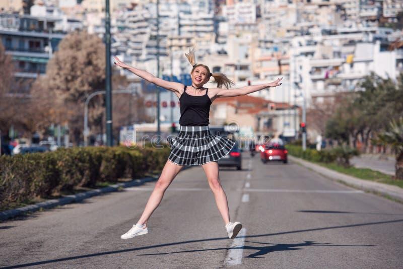 La mujer rubia con las pequeñas coletas salta en el medio de una carretera rápida foto de archivo